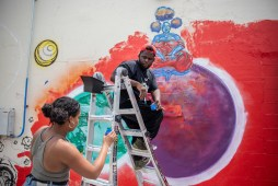 "Krystal ""Gem"" Jackson, left, and Kwame Braxton share paint as they create murals on the Center for Community Production building in downtown Jackson Wednesday, April 17, 2019."
