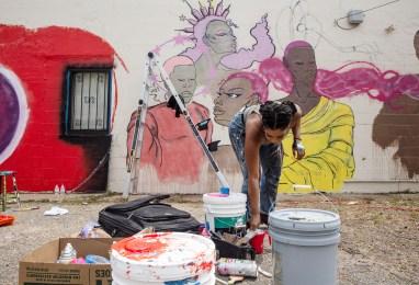 "Krystal ""Gem"" Jackson chooses paint as she works on her mural during Mural Fest in Jackson, Miss., Wednesday, April 17, 2019."