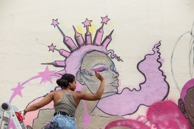 """Krystal """"Gem"""" Jackson stops painting to wave at children as they pass during Mural Fest in Jackson, Miss., Wednesday, April 17, 2019."""