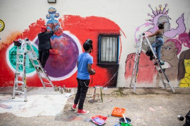 """Martie """"Ayce"""" Gooch, of Nashville, Tenn., watches as Kwame Braxton, left, and Krystal """"Gem"""" Jackson create murals on the Center for Community Production building as a part of Mural Fest in downtown Jackson Wednesday, April 17, 2019."""