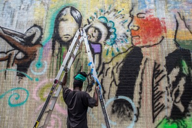 Shambé Jones works on a mural depicting indigenous people during Mural Fest in downtown Jackson, Wednesday, April 17, 2019.