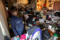 Elizabeth Coats examines the conditions of her Tchula home May 9, 2019 following recent flooding. Clothing, purses, linens, newspapers, notebooks, toiletries, electronics and picture frames overwhelm every surface in her trailer, including a brown striped sectional. While recent floodwaters did not enter the inside of Coats' dilapidated home, it looks like they could have.