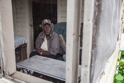 Geneva Williams looks out of the screen door as she sits on her front porch at her home in Tchula, Miss., Thursday, May 9, 2019.