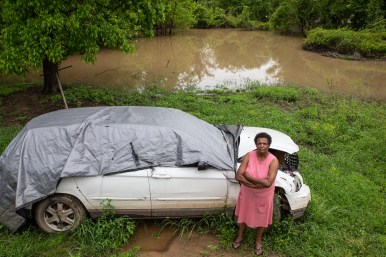 Jennie Jefferson stands near her car, which was damaged by the flooding, in Tchula, Miss., Thursday, May 9, 2019. Jefferson is still making payments on her car, but she is unable to afford repairs.