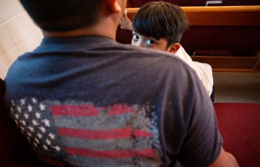 """Doroteo Lopez holds his 5-year-old son Lesvi Lopez during the Poor People's Campaign's """"Everybody's Got a Right to Live"""" mass at Liberty Missionary Baptist Church in Canton, Miss., Thursday, Aug. 29, 2019."""