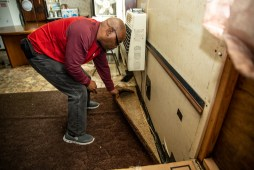 Anthony Burkett lifts to carpet to look at the damaged floors that could possibly contain mold in Seminary, Miss., Wednesday, October 30, 2019. Burkett is a U.S. Army veteran. He was injured in a car accident in the mid 80s, which left him disabled.