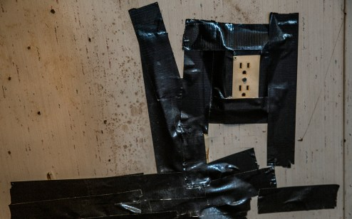 Electrical tape holds an electrical socket to the wall inside of U.S. Army veteran Anthony Burkett's trailer in Seminary, Miss., Wednesday, October 30, 2019.