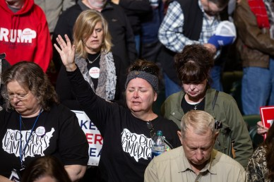 An audience member raises her hand during prayer at a campaign rally in the BancorpSouth Arena in Tupelo, Miss., Friday, November 1, 2019.