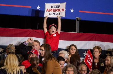 """A young boy holds a """"Keep America Great!"""" sign during the Trump rally at BancorpSouth Arena in Tupelo, Miss., Friday, November 1, 2019."""