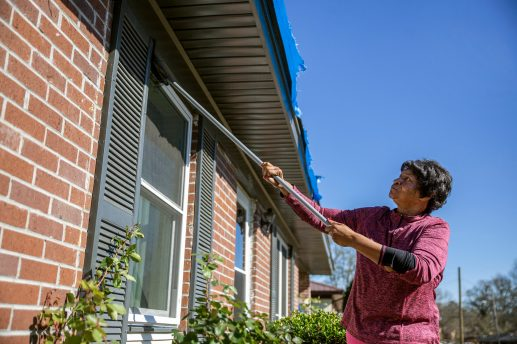 Nadine Lomax removes dirt from the windows of her home Thursday, December 19, 2019, after Monday's tornado that touched down in Edwards, Miss.