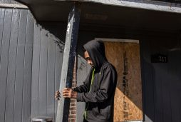 Zachary Davenport tries to straighten a column on his mother's home which had fallen after Monday's tornado in Edwards, Miss.