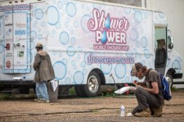 Timothy Riles enjoys as meal outside of the Shower Power Mobile Unit in the 800 block of South Commerce Street in Jackson, Miss., Friday, April 3, 2020.