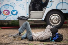 A homeless man rests outside of the Shower Power Mobile Unit in the 800 block of South Commerce Street in Jackson, Miss., Friday, April 3, 2020.