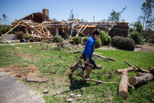 Collin Sanderson picks up debris at his grandfather's home in Bassfield, Miss., Tuesday, April 14, 2020.