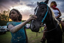 Bree Gary pets her friend's horse during a muddy trail ride in Charleston — 2019.