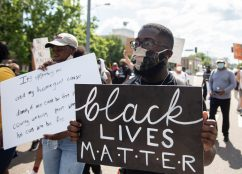 Protesters hold signs as they march during the Black Lives Matter protest in downtown Jackson, Miss., Saturday, June 6, 2020.