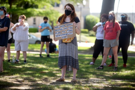 Nellie Massey, a first year Jackson Public School District teacher, holds a sign outside of the Capitol in Jackson during a protest against reopening Mississippi Schools Friday, July 17, 2020.