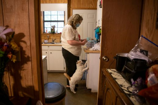 Whitney Wages feeds her cat, Wilson, in her apartment outside of Oxford, Mississippi. Less than a week earlier, her landlord Wilma Hughes told Wages she must vacate her home, which means finding a new, one-floor apartment that she can afford and that will accept her housing voucher.
