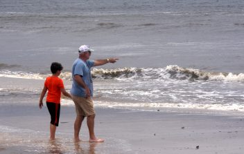Jacob Thornton and Jimmy Putnam wade out to get a closer look at waves crashing ashore in Biloxi Tuesday afternoon. Hurricane Sally turned toward Mobile, Ala., taking the eye off the Mississippi Gulf Coast.