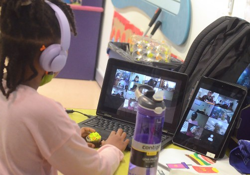 Kaylen Wade, 8, uses a laptop and tablet to participate in class via Zoom while at the Mississippi Children's Museum.
