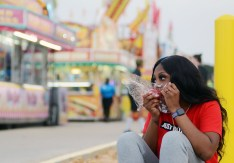 Dacia Wilchur of Jackson, finds a quiet spot away from the crowds to enjoy a candy apple.