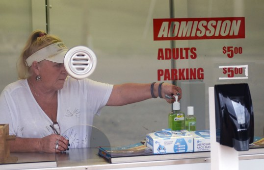 Gate 1 ticket taker Candi Lewis uses hand sanitizer after selling admission tickets at the Mississippi State Fair on Thursday afternoon. Hand sanitizer stations are placed throughout the fair. Face masks are provided for fair-goers needing one.
