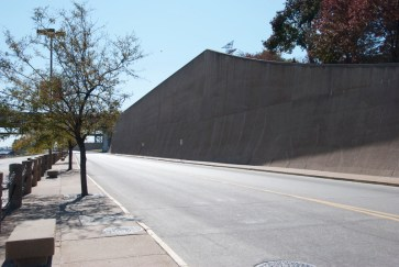 A giant concrete wall separates the Arch from the riverfront