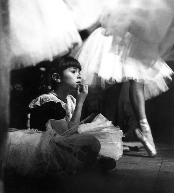 """Bonnie Patterson sitting in the wings watching the rehearsals of """"The Children's Ballet Co."""", Los Angeles, 1953"""