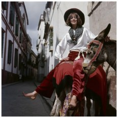 model-riding-a-donkey-in-spain-wearing-claret-velvet-trousers-with-wide-legs-a-white-satin-gypsy-blouse-with-gathered-voluminous-sleeves-both-by-anne-klein-a-printed-scarf-and-a-burgu