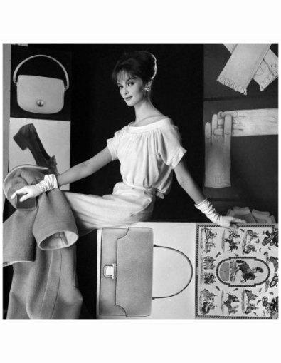 Madame Grès (1903-1993). Robe en jersey de laine blanc. Clips d'oreilles Vendôme. Sur le panneau photographique : un sac plat en porc à fermoir plaqué or et un carré en soie imprimée de motifs équestres or, bruns et gris. Hermès. Les coiffures ont été créées par Alexandre. Printemps-été 1961. Photographie d'Henry Clarke (1918-1996), publiée dans Vogue France, mars 1961, p. 219. Galliera, musée de la Mode de la Ville de Paris. Dimensions : 6 x 6