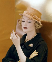 ca. 1959 --- Model wearing hat of feathers, worked to look like silk, in a pale orange, by Adolfo of Emme. Worn with brown wool tweed coat, pinned with Verdura brooch. --- Image by © Condé Nast Archive/CORBIS
