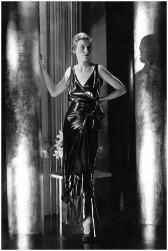 Model Bettina Jones wearing a Schiaparelli Pinafore evening dress of cir� satin with a bow on the side and a low V-neckline which extends to the waist in the back; Model stands between columns with gilt-like finish and low table with vase of flowers behind