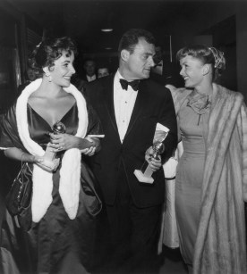 28th February 1957: From left to right, British-born actor Elizabeth Taylor and her husband, film producer Mike Todd (1909 - 1958), hold their Golden Globe awards while walking with American actor Debbie Reynolds at the Hollywood Foreign Press Association Awards Dinner in Los Angeles. Taylor won a special award for consistent performance, and Todd produced Michael Anderson's 1957 film, 'Around the World in Eighty Days,' which received the Best Motion Picture- Drama award. (Photo by Darlene Hammond/Hulton Archive/Getty Images)