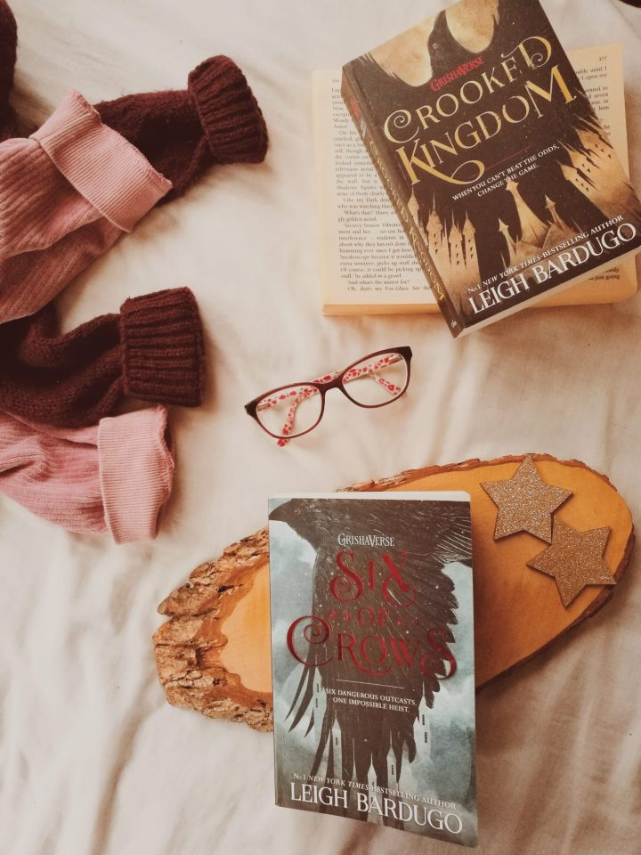 six of crows book with jumpers/ sweaters around it and crooked kingdom for this review.