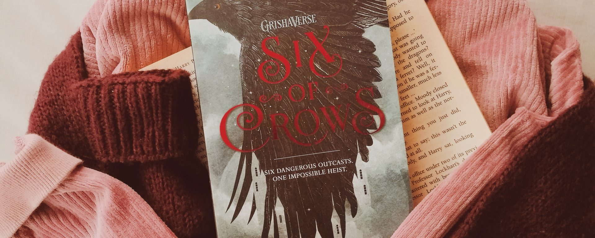six of crows book with jumpers/ sweaters around it and the quote no mourners no funerals above for this review.