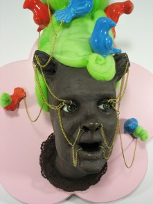 "Fashion Victim #5, 2010, clay, paint, chain, glaze, lace, wood, 27"" x 17"" x 13"""