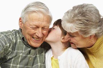 child kissing grandparents