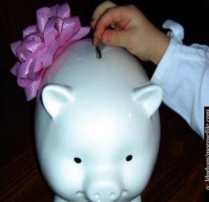 child putting money in a piggy bank