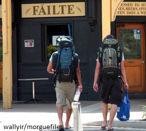 Two backpackers facing away from camera walk toward Irish pub