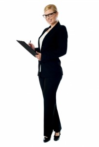 A woman in a suit holding a clipboard