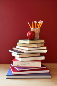 a pile of books with an apple and pencils