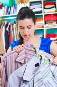 a woman in a closet holding shirts on hangers with one hanger in her teeth