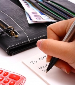 wallet on the table and a female hand writing down a shopping list