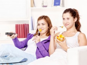 two girls sitting in the living room, watching movie, eating fruit