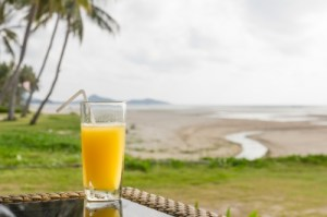 glass of orange juice on the beach