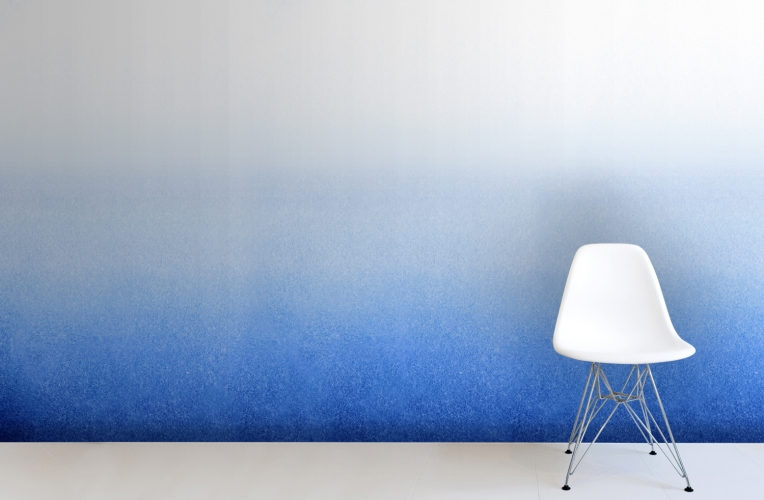 A white chair against an indigo ombre mural.