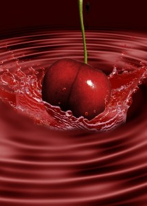 cherry being dropped into tart cherry juice food to be beautiful