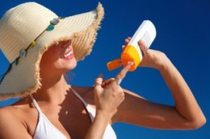 woman in sun hat applying sunscreen against a blue sky