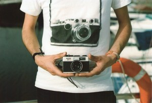 guy wearing a camera tshirt and holding a camera