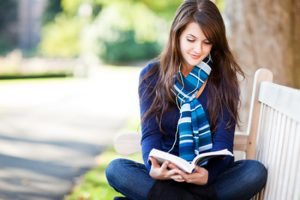 college girl sitting outside reading with headphones in listening to music